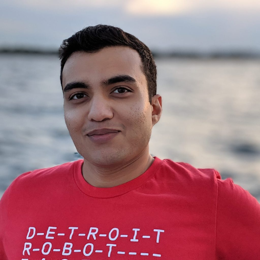 In this picture, Ninad is smiling warmly with the Detroit River in the background. The lighting is great and he is wearing a red Detroit Robot Factory t-shirt.