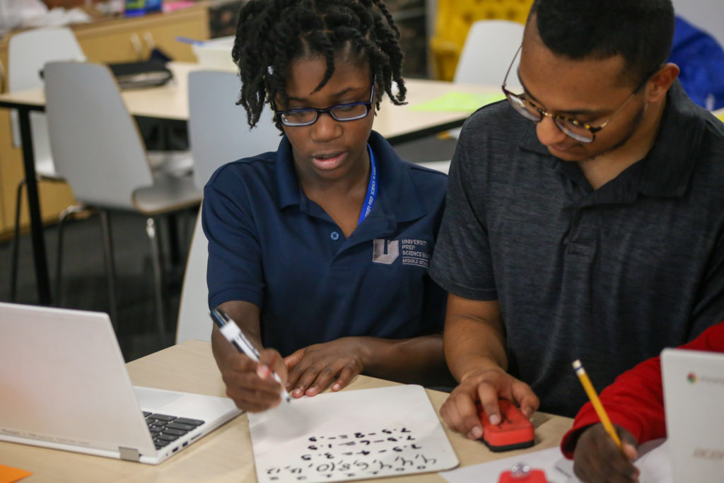 a long time tutor helps a student with her math homework in detroit